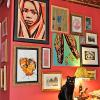 For a NYC apartment an eclectic wall grouping of different types of art against a red wall.